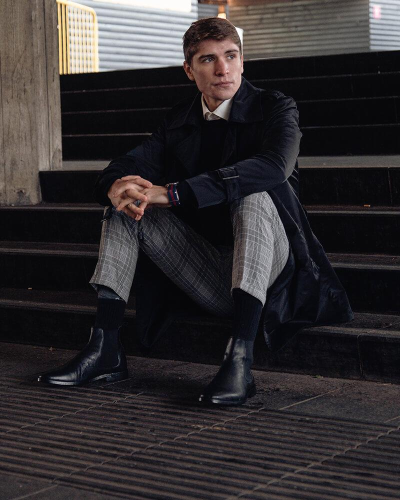 chàng trai mặc áo đen, quần tây xám và giày chelsea boots đen.