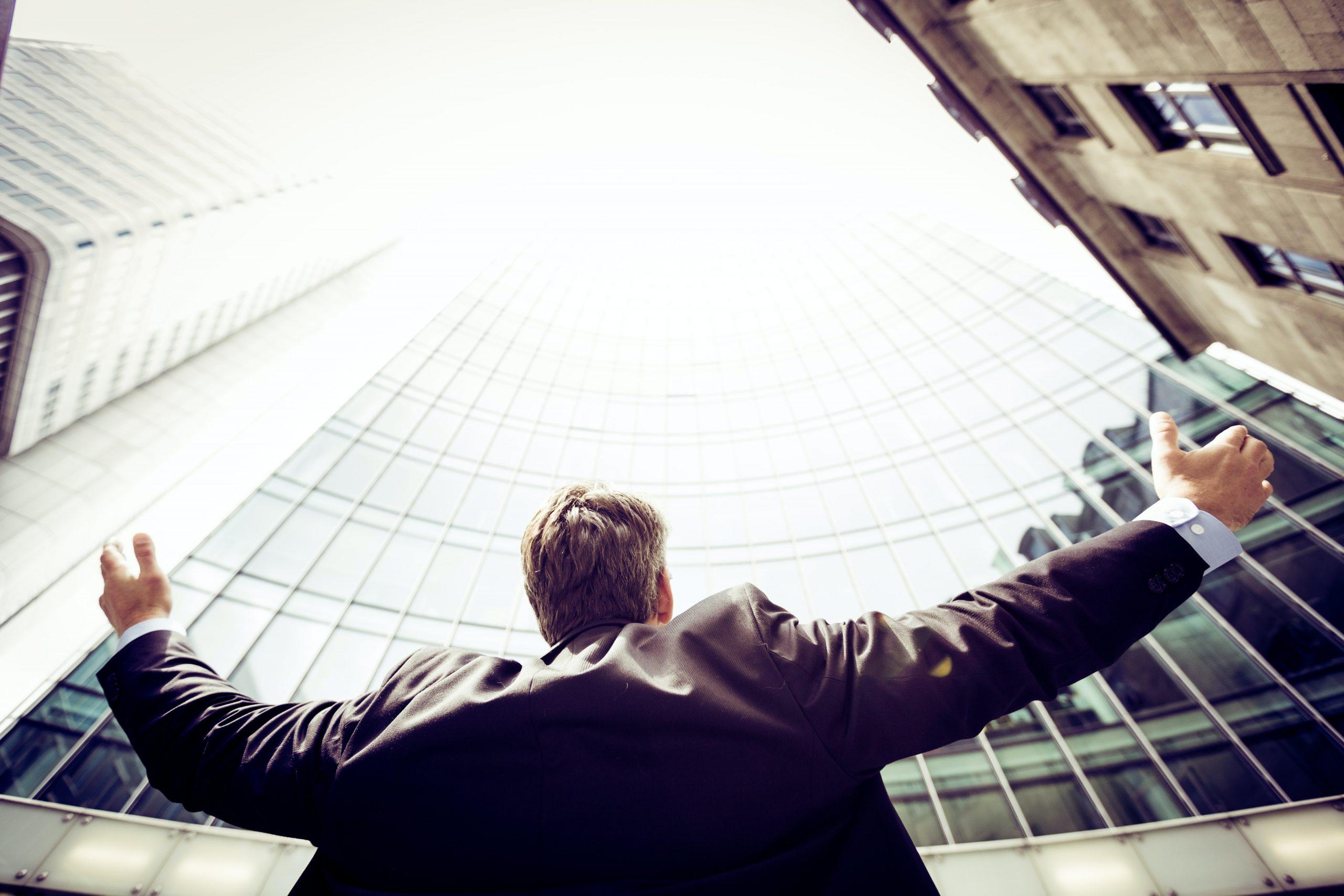 người đàn ông thành công dang tay nhìn lên trời.