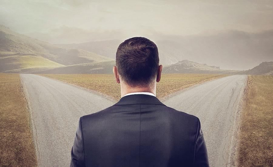 người đàn ông đứng giữa ngả 2 con đường.