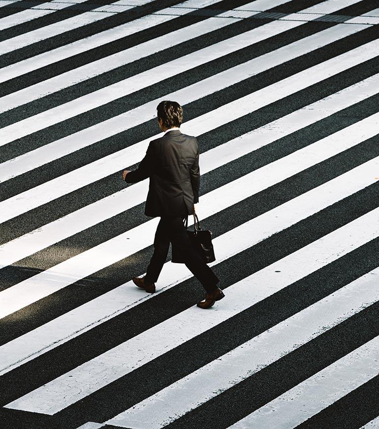 người đàn ông băng qua đường trên vạch vôi.