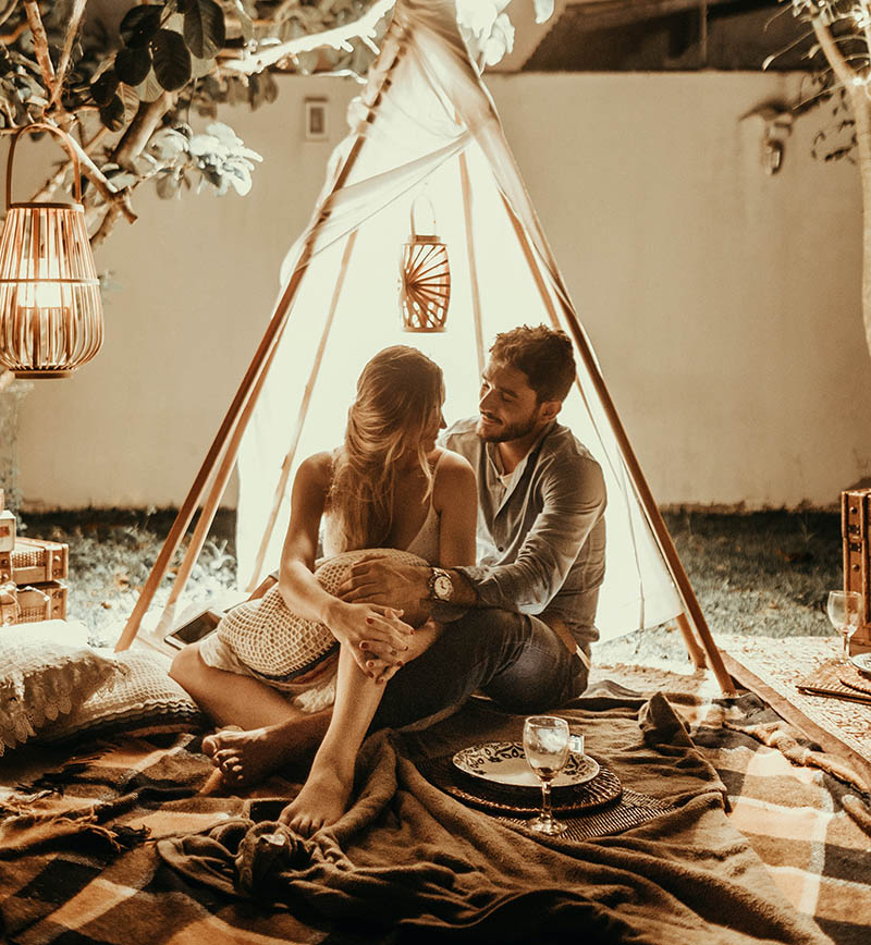 cặp đôi ngồi ôm nhau trong túp lều.