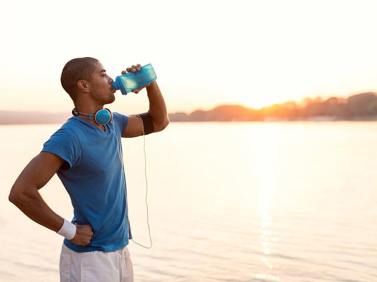 người đàn ông uống nước khi tập thể dục.