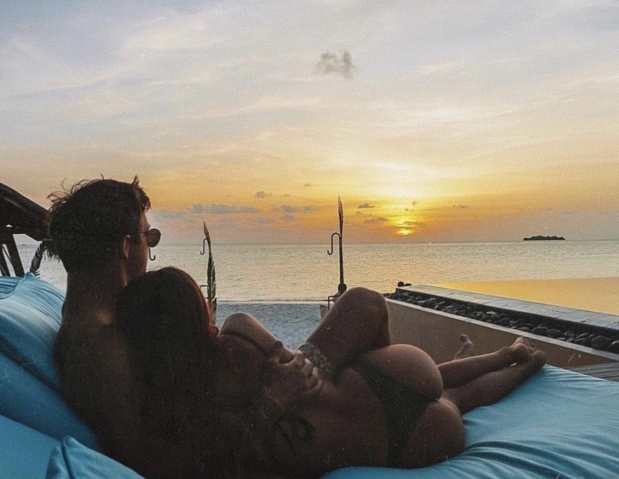 cặp đôi ôm nhau đón bình minh trên biển.