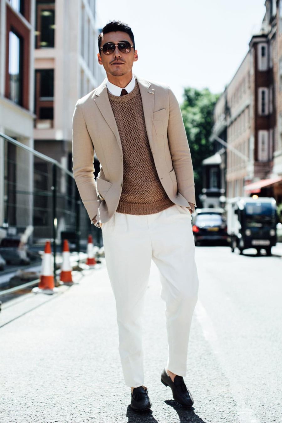 người đàn ông mặc vest trắng đi trên phố